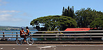 A couple doubles on a bicycle as they cross a bridge near the Suisan Market in Hilo on the Big Island, Hawaii.