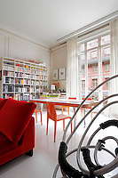 A massive bookshelf by Shiro Kuramata in the living area dominates a table by Pucci de Rossi surrounded by orange chairs by Riccardo Blumer