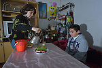 Roaa Sabah pours tea for her 10-year old son Behnam as he prepares to leave for school early in the morning from their home in Seje, Iraq. The community was flooded with displaced families when the Islamic State group took over nearby portions of the Nineveh Plains in 2014, including this family, which fled from Mosul to eventually live in a small, manufactured housing unit in Seje. Because Behnam and other displaced children came from communities with Arabic curriculum schools, they don't fit well in local schools that teach in Kurdish or Assyrian, so the Christian Aid Program Nohadra - Iraq (CAPNI) provides transportation for them to Duhok, where they study in schools that meet their needs.