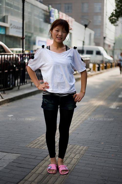 Zhangli, a supermarket clerk, age 23, poses for a portrait in Nanjing. Response to 'What does China mean to you?': 'Very good. Very beautiful. Very big.'  Response to 'What is your role in China's future? or What is China's role in the future?':'[no answer]'