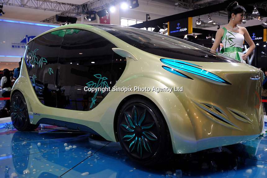 "A model poses next to an IAT (International Application Technology) ""Zu"" electric concept car, designed by IAT (China) Automobile Technology, at the Beijing Auto Show in Beijing, China. The car show has attracted all the world's major auto markers. China's vehicle sales have breached the 10-million barrier for the first time ever, with 10.9 million automobiles sold last year. .24 Apr 2010"