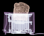 X-ray image of a toaster with bread (color on black) by Jim Wehtje, specialist in x-ray art and design images.