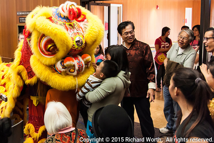 Lion dancers of the Vovinam Viet-Do-Dao of San Jose engage with spectators, including this youngster and his mother, during Lunar New Year festivities in San Leandro, California.