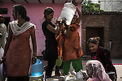 Priyanka Jena (right) speaks to her neighbours who are seen collecting water in Sangam Vihar in New Delhi, India. Photo: Sanjit Das for The Foreign Policy
