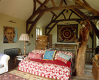 The large living room in the converted barn is decorated with an ethnic wall hanging, an abstract portrait painting and a wooden sculpture