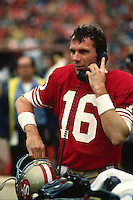 SAN FRANCISCO, CA - Quarterback Joe Montana of the San Francisco 49ers talks on the telephone during a game at Candlestick Park in San Francisco, California in 1988. Photo by Brad Mangin