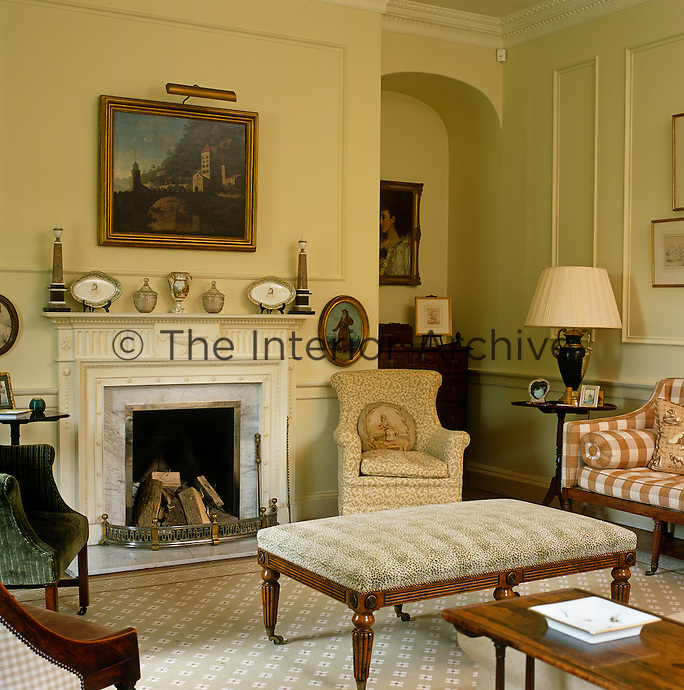 The comfortable drawing room has a Victorian marble fireplace around which is grouped a variety of upholstered armchairs and antiques