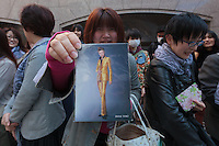 A woman hold a postcard with a note to her favourite Takarazuka actress, Toki Irizu, on it as she waits outside the Takarazuka theatre in Hibiya for the stars of the show to arrive. Tokyo, Japan. Sunday March 29th 2015 Takurazuka Theatre is an all female musical theatre group that put on melodramatic and romantic shows for a mostly female audience.