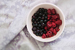 A bowl sitting on a purple sheet with half blue berries and half raspberries.