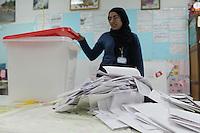 23 ottobre 2011 Tunisi, elezioni libere per l'Assemblea Costituente, le prime della Primavera araba: durante lo scrutinio una giovane donna Osservatore Nazionale apre l'urna. Sul tavolo sono appoggiate le schede elettorali.<br /> premieres elections libres en Tunisie octobre <br /> tunisian elections