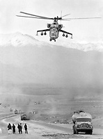 "A Soviet Mi-24 ""Hind"" attack helicopter escorts a fuel convoy on its way to the Afghan capital Kabul on Sunday, February 5, 1989. Under siege for several years, the regime in Kabul depends heavily on Soviet military support."
