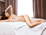 Artistic photo of a beautiful young asian woman lying naked on a bed by the window