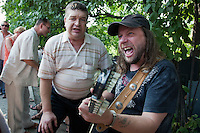 Moscow, Russia, 25/07/2010..Two men sing songs by Vladimir Vysotsky as hundreds of Russians gather at the grave of the legendary bard singer, poet and actor  to mark the 30th anniversary of his death. Vysotsky, an alcoholic and heroin addict who died in 1980 aged 42 of a heart attack, is best known for his songs of Soviet prison and military life, and his acting on stage and screen. Much of his work was officially unpublished during his lifetime, and he remains a potent anti-authoritarian symbol of protest to Russians of all ages even today.