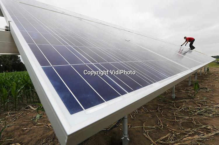 Foto: VidiPhoto<br /> <br /> SOMEREN - Personeel van Solateur New Energy Systems installeert donderdag bij het akkerbouwbedrijf van Joep Veldkamp in Someren (Noord-Brabant) een vijftigtal zonnepanelen op een stellage in een zogenaamde vrijeveld-opstelling. Veldkamp maakt gebruik van het samenwerkingsverband van boeren in het project LTO Energie. Door co&ouml;peratief zonnepanelen aan te schaffen wordt zo'n 20 procent bespaard op de inkoop. Het initiatief van LTO blijkt een groot succes. Ruim 450 agrarische bedrijven namen deel in ronde 2. De zonnepanelen van Veldkamp zorgen voor 14.000 kWh aan energie en dat is wat hij jaarlijks ongeveer verbruikt. Behalve agrari&euml;rs gaan ook steeds meer particulieren over tot het plaatsen van zonnepanelen.