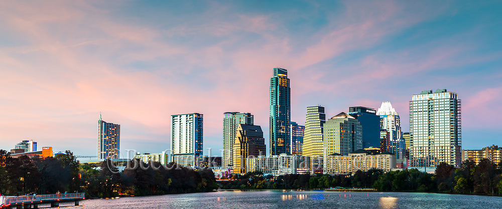 We captured this panorama photo of the Austin skyline at dusk as the sky lights up with this great pinks sky as the sunsets over the downtown from the hike and bike area of Ladybird Lake or town lake as some call it in downtown.  It is always a treat when you get a colorful sky around sunset because so many times the clouds blow off right at this time and you miss out on all the nice colors that the clouds pick up as the sunsets.  This area is the of the boardwalk which connects hike and bike area of the downtown with the east side of the lake trails has become a popular spot for catching the skyline of the city because the other areas have some many cranes it will be years before they are finished.  However that is not a guarentee that the crane will be gone because there are always plans for more new buildings in the downtown area especially along the town lake.