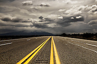 Storm clouds over US highway 550 with the Sandia Mountains in the distance in north-central New Mexico.