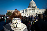 Hundreds of protestors with the Occupy movements gather outside the Capitol, waving signs and chanting against a barrier of police.