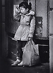 A young girl in tears waits outside a local grocery store for her parents in the tenderloin district of San Francisco, California.