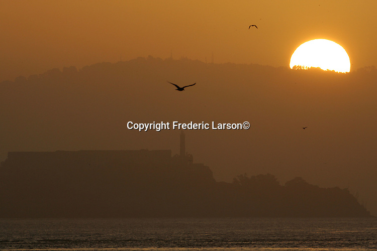 The sunrises over the East Bay hills and Alcatraz Island as seen from Fort Point in San Francisco, California.