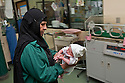 An Iraqi nurse carries a newborn baby from the neonatal wing of the Khadamiyah hospital in Baghdad August 25, 2010. After seven years of conflict,  Iraqi hospitals continue to be overcrowded, in a state of disrepair and stocked with old or outdated medical equipment.   .