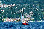 Red sailboat in front of Varenna, Italy on Lake Como
