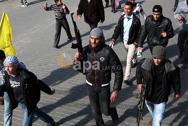 A Palestinian gunman fires into the air during the funeral of Anwar Al-Mamlouk in Gaza City January 12, 2013. Israeli army gunfire killed Mamluk and wounded another man in the northern Gaza Strip, a spokesman for the territory's emergency services said. Photo by Ashraf Amra