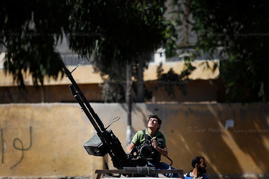 Free Syria Army soldiers attempt to hit a fighter jet with a  Russian Dushka machine gun as the aircraft turns to make another bombing drop in a populated neighborhood in Aleppo...© Javier Manzano