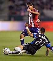 Chivas USA forward Jesus Padilla (10) attempts to move past sliding San Jose Earthquakes defender Jason Hernandez (21). CD Chivas USA defeated the San Jose Earthquakes 3-2 at Home Depot Center stadium in Carson, California on Saturday April 24, 2010.  .