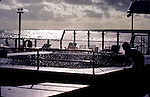 Crew member silhouetted adjusting net across  the swimming pool on cruise ship