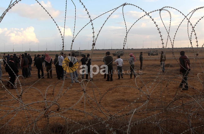 Palestinians stand near the Israeli Gaza border fence in east of Khan Younis, southern Gaza Strip, Friday, Nov. 23, 2012. Hundreds of Gaza crowds surged toward Israel's border fence with the Hamas-ruled territory, in a no-go-zone that has been kept by Israel for years to prevent infiltrators. The crowd, many returning to their farm land, were testing new agreements mediated by the Egyptians between Hamas and Israel that led to a cease-fire after eight days of cross-bordering fighting. One Palestinian was killed and 19 injured. Photo by Ashraf Amra