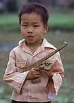 A youngster has a purposeful plaything as he cradles as proudly as an honor gurad - sticks nailed together to form an AK-47 assault rifle in Hanoi, North Vietnam. (Jim Bryant Photo).....