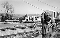 An elderly Sarajevo man carries a bag of firewood and an axe in the western part of the besieged Bosnian capital on December 3rd, 1992. Sarajevo, where temperatures drop below freezing has been without electricity, gas and running water since April 1992. The only trees left standing are in areas dangerously exposed to sniper fire.