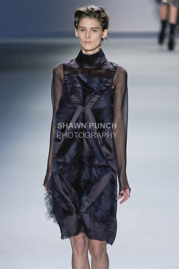 Marie Piovesan walks runway in a plum silk chiffon long sleeve dress with high neck and multi-layer silk tulle flange detail over plum silk chiffon boy short, from the Vera Wang Fall 2012 Vis-a-gris collection, during Mercedes-Benz Fashion Week Fall 2012 in New York.