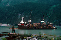 731000334 a working logging ship the haida brave loaded floating logs or timber slowly makes its way through the bay for lumber transport to international destinations stewart bay british columbia canada - image is not property or model released