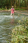 Woman crossing the Wailua River with a rope on her way to Secret Falls, Kauai, Hawaii