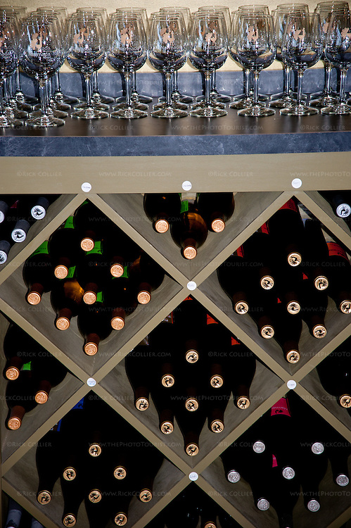Bins of wines are neatly stacked beneath an enormous supply of tasting glasses on display behind the bar at Narmada Winery.