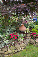 Pretty raised bed shaded garden, Japanese painted ferns, impatiens, coleus, decorative pots, birdhouse, Japanese maple tree, hostas, patio, Pulmonaria and lamium groundcovers, pots, decorations, flowers and foliage plants, lawn grass.