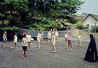 Saint John Villa Academy, NY. Nun teaching young girls how to play volleyball.