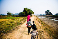47 year old Sampat Pal Devi, founder and leader of the 10,000 strong Gulabi Gang, walks down a rural road in Banda. In the badlands of Bundelkhand, one of the poorest parts of one of India's most populous states, a gang of female vigilantes have sprung up to fight the oppression of a caste-ridden, feudalistic and male dominated society. In a land where dowry demands and domestic and sexual violence are common, the 'Gulabi Gang' (Pink Gang), so called for their uniform of shocking pink saris, are picking up their lathis (traditional Indian sticks) to fight against corruption and violence against women.