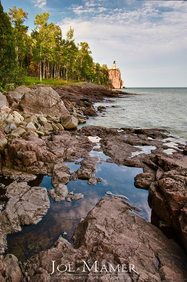 The shore of Lake Superior a short distance from Split Rock Lighthouse. Split Rock Lighthouse is located southwest of Silver Bay, Minnesota, USA on the North Shore of Lake Superior. The structure was designed by lighthouse engineer Ralph Russell Tinkham and was completed in 1910 by the United States Lighthouse Service at a cost of $75,000, including the buildings and the land. It was built in response to the loss of ships during the famous Mataafa Storm of 1905, in which 29 ships were lost on Lake Superior.[3] One of these shipwrecks, the Madeira, is located just north of the lighthouse. The light was first lit on July 31, 1910.