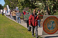 "Mohammed holds the ""Occupy Orange County"" sign as Occupy Orange County, Irvine marchers walk down the sidewalk of Alton in Irvine, CA as a part of their Saturday protest against banks.  Many signs are visible."