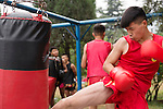Sanda, Chinese boxing student practicing kicks on a punching bag in DengFeng, ZhengZhou, Henan, China 2014