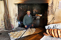 """Baker looking at the camera inside his traditional bakery with fresh baked bread in the foreground and the oven in the background, old city, Portuguese Fortified city of Mazagan, El Jadida, Morocco. El Jadida, previously known as Mazagan (Portuguese: Mazag""""o), was seized in 1502 by the Portuguese, and they controlled this city until 1769. Picture by Manuel Cohen"""