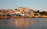 View of the medieval city of Coimbra seen from across the Mondego river, with the University of Coimbra at the summit, with its clock tower, Coimbra, Portugal. The University of Coimbra was first founded in 1290 and moved to Coimbra in 1308 and to the royal palace in 1537. The city dates back to Roman times and was the capital of Portugal from 1131 to 1255. Its historic buildings are listed as a UNESCO World Heritage Site. Picture by Manuel Cohen University of Coimbra, Coimbra University, university, clock tower, library, General Library