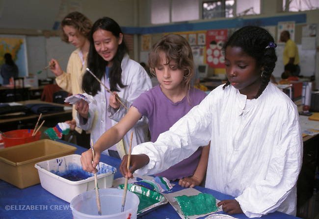 Berkeley CA 5th grade girls doing art project in class, making masks.  Shows different developmental heights around age eleven years