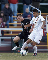 Boston College defender Kevin Mejia (12) dribbles as Brown University forward Ben Maurey (13) pressures. Brown University (black) defeated Boston College (white), 1-0, at Newton Campus Field, October 16, 2012.