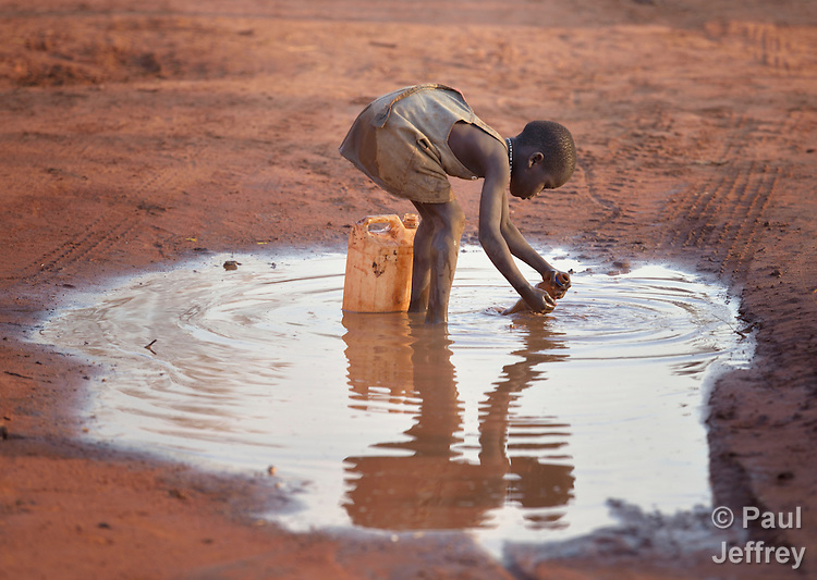 A girl fills a container with muddy water in the Ajuong Thok Refugee Camp in South Sudan. The camp, in northern Unity State, hosts thousands of refugees from the Nuba Mountains, located across the nearby border with Sudan.