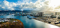 An aerial view of Honolulu Harbor and Ward/Kaka'ako area at sunrise; two cruise liners are docked at the harbor and light rays cascade down from the east.