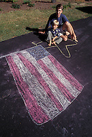Father and young son with patriotic chalk drawn flag on asphalt drive way.