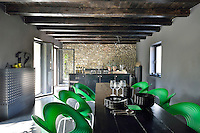 An open plan kitchen/dining space with grey painted walls and a low beamed ceiling. In the dining area is a dark wood table and green moulded plastic chairs.